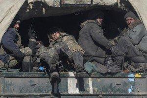 Ukrainian servicemen ride on a military vehicle as they leave area around Debaltseve