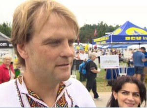 Chris Alexander at Ukraine Independence Day event in Toronto, Aug 2014. In background are red-black flags of Ukraine far-right
