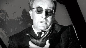 Peter Sellers playing Dr. Strangelove in the 1964 film of that name. Dr. Strangelove struggles to control his right arm from making a Nazi salute
