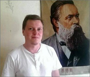 Victor Shapinov, beside a portrait of Frederick Engels