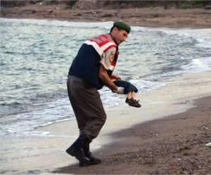 Turkish official recovers the body of Alyan Kurdi, one of two children who drowned on Sept 3, 2015 while fleeing the war in Syria with their mother and father (DHA photo)