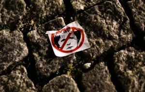 In this Oct. 12, 2015 photo a sticker with a drawing of German Chancellor Angela Merkel sits on a sidewalk after a demonstration of PEGIDA (Patriotic Europeans against the Islamization of the West) passed the street in Dresden. (AP Photo/Markus Schreiber)