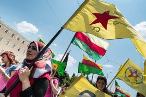 Kurdish women hold flags of YPG (People's Protection Units) and Rojava territory in front of Greek parliament on July 16, 2015 (Andreas Solaro, AFP)