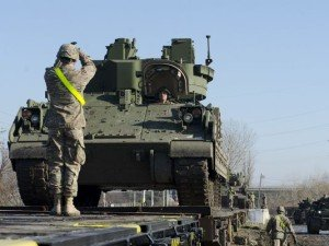U.S.soldiers load a Bradley Fighting Vehicle onto a train in Romania on Dec 3, 2015 (U.S. Army photo)