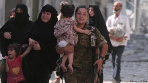 Woman SDF fighter helps evacuate civilians from last neighbourhood in Manbij, Syria controlled by ISIS (Rodi Said, Reuters)