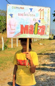 A young communard carries a sign celebrating the 11 years of the El Maizal Commune.